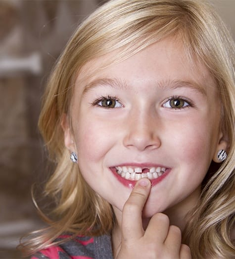Little girl pointing to gap left by extracted tooth