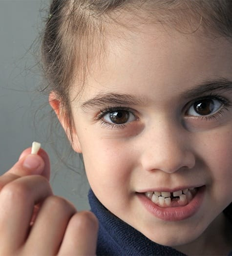 Little girl holding her extracted tooth