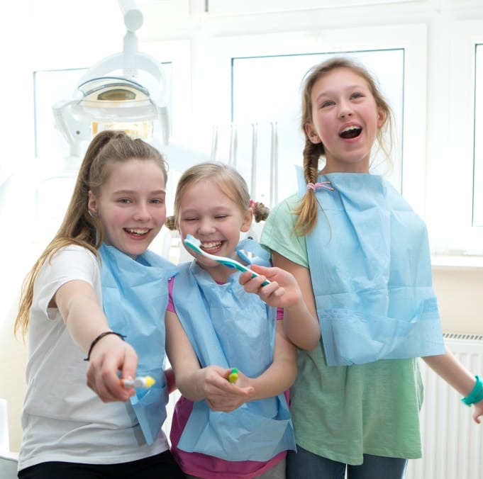 Three young girls practice tooth brushing at pediatric dentistry visit