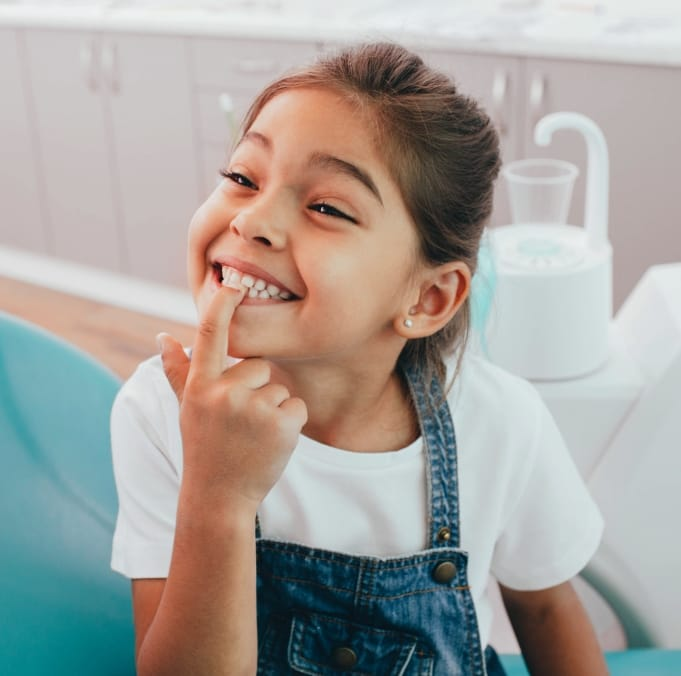 Child pointing to her smile after amalgam free dental filling
