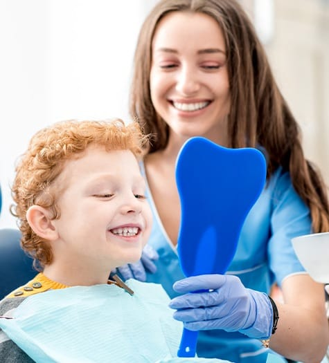 Little boy looking at smile after teeth cleaning
