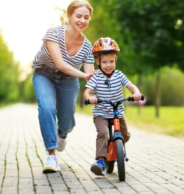 Mother helping little boy learn to ride his bike after emergency dentistry visit