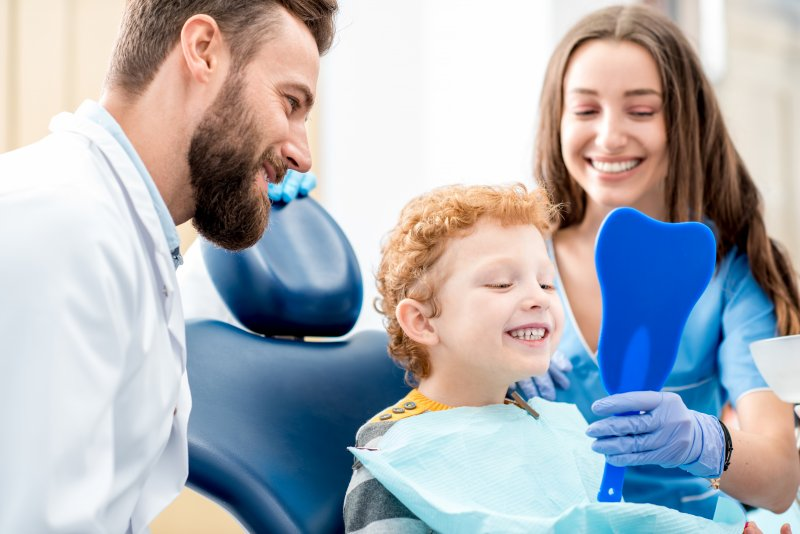 a dentist and dental hygienist showing a little boy his smile after a general checkup