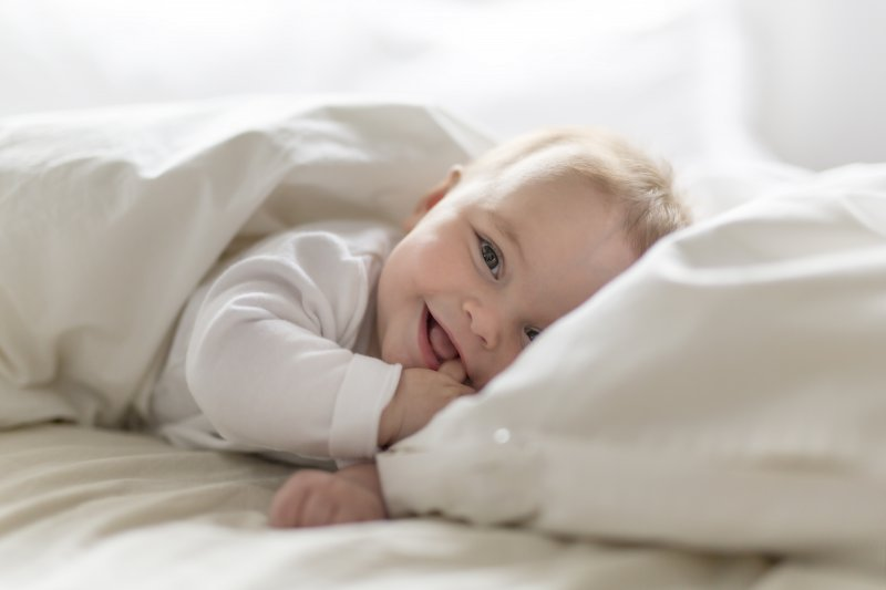 Baby smiling while lying in bed