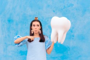 Tooth Fairy in Garland pointing to model tooth