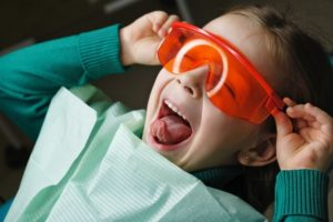 child smiling as they're having dental sealants in Garland placed in their mouth