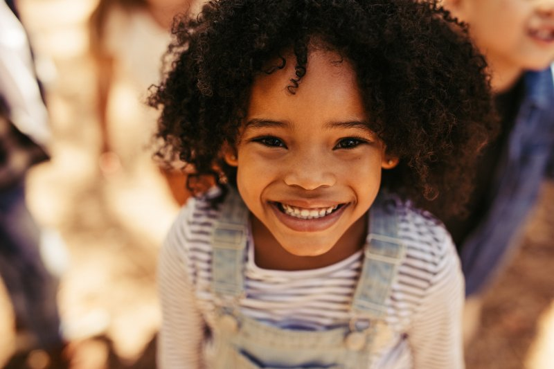 a little girl wearing denim overalls and showing off her healthy, beautiful smile