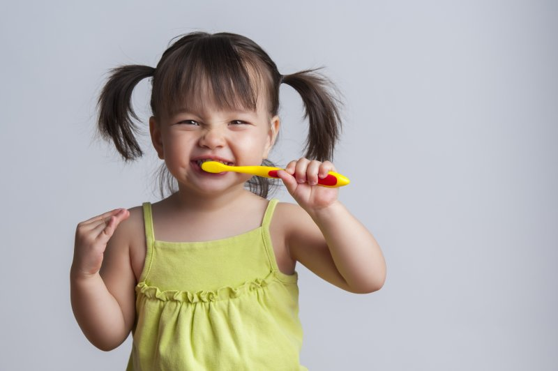 a little girl with pigtails using a manual toothbrush to clean her teeth