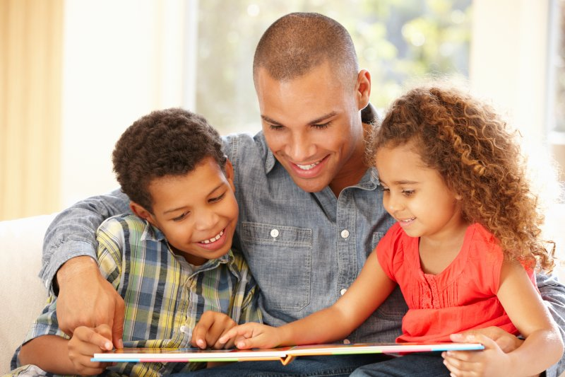 a father reading to his two children about visiting the dentist