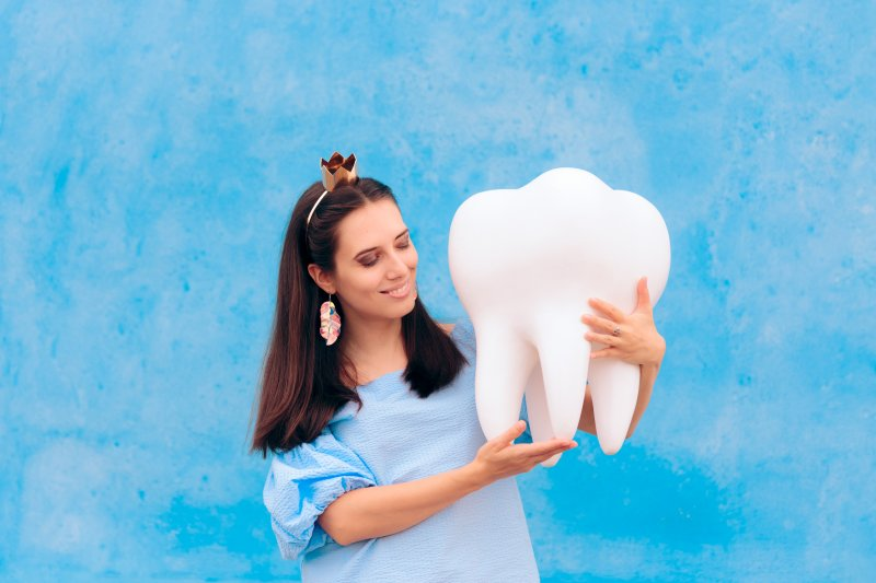 Tooth fairy holding a large tooth mold in Garland
